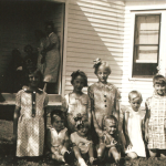 These Schmidt/Lindemann children were photographed in July 1937 at the 50th wedding anniversary celebration of Mike & Lizzie (Schmidt) Lindemann, on the farm of their son Carl Lindemann, near Humboldt, Iowa.  The only faces identified with certainty are Marvin Lindemann (1934-Present) (on the far left of the front row), and Carol Lindemann (1929-2003) (on the far right of the back row).  Marvin and Carol were the children of Carl Lindemann, grandchildren of Lizzie (Schmidt) Lindemann, great grandchildren of Conrad Schmidt, 2xgreat grandchildren of Dietrich Schmidt Sr., 3xgreat grandchildren of Friedrich Schmidt, 4xgreat grandchildren of Johannes Schmidt Jr., 5xgreat grandchildren of Johannes Schmidt Sr., 6xgreat grandchildren of Hans Heinrich Schmidt, and 7xgreat grandchildren of Hans Schmidt.  Photo courtesy of Denise Lindemann