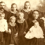 "(Left to right)  (Back row) Michael ""Mike"" Lindemann (1860-1951); Martha Elizabeth Lindemann (1889-1909); Anna M. Lindemann (1888-1974).  (Front row) John Michael Lindemann (1893-1941); Elizabeth Katharina ""Lizzie"" Lindemann (1895-1993); Marie Anna ""Mary"" Lindemann (1894-1965); Katharina Elisabeth Martha ""Lizzie"" (Schmidt) Lindemann (1895-1993); Conrad Jacob ""Connie"" Lindemann (1891-1925).  (On Lizzie's lap) Carl Michael Lindemann (1898-1991).  These kids were the children of Mike and Lizzie (Schmidt) Lindemann (both pictured here). These kids were the grandchildren of Conrad Schmidt, great grandchildren of Dietrich Schmidt Sr., 2xgreat grandchildren of Friedrich Schmidt, 3xgreat grandchildren of Johannes Schmidt Jr., 4xgreat grandchildren of Johannes Schmidt Sr., 5xgreat grandchildren of Hans Heinrich Schmidt, and 6great grandchildren of Hans Schmidt.  Photo courtesy of Denise Lindemann"